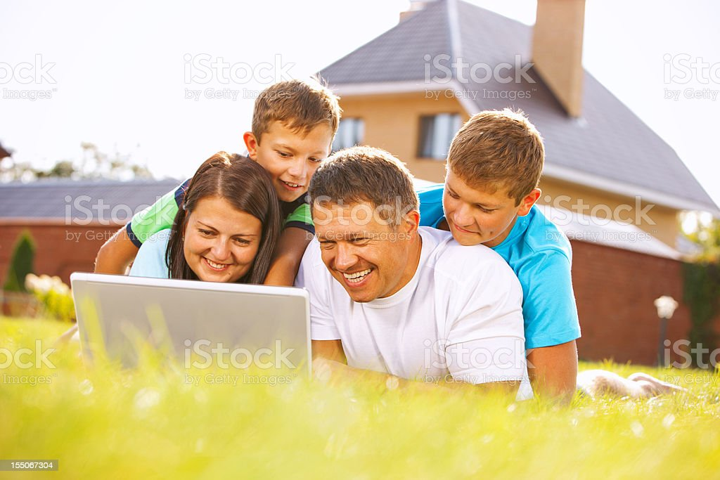 Family with two children using laptop lying on grass royalty-free stock photo