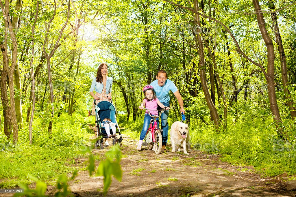 Family With Two Children Walking and cycling in a forest. royalty-free stock photo