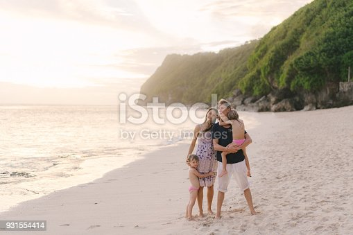 929671306 istock photo Family  with two daughter  walking on the beach 931554414