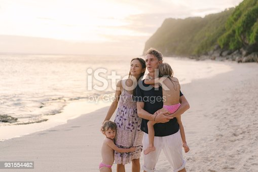 929671306 istock photo Family  with two daughter  walking on the beach 931554462