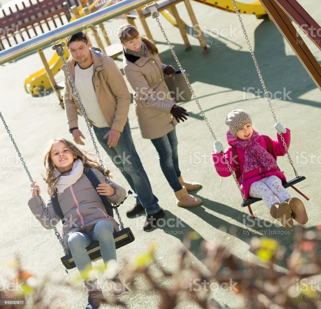 Família com Duas garotas se divertindo ao ar livre no balanço - foto de acervo