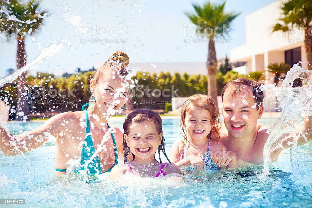 Family with two kids having fun in the swimming pool stock photo