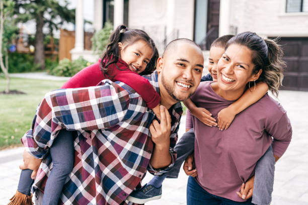 Family with two kids looking at camera Parents carrying children piggyback outdoor filipino ethnicity stock pictures, royalty-free photos & images