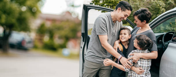 Family with two kids . Moment with hugs near car stock photo