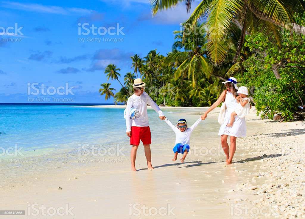 family with two kids playing on beach stock photo