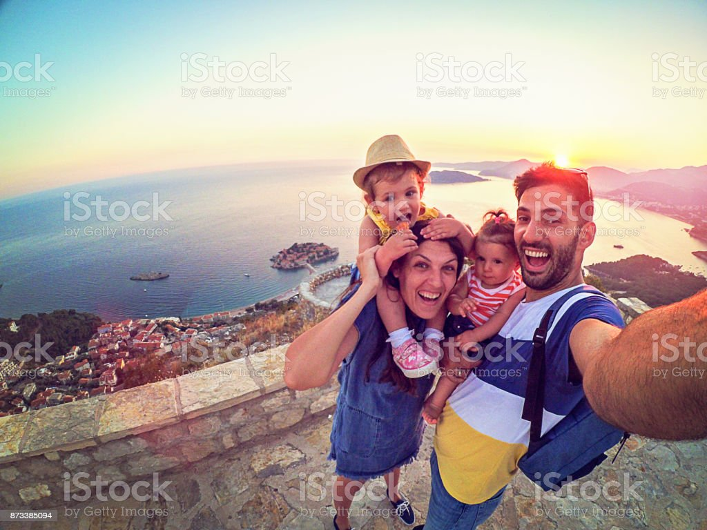 Family with two little daughters travel in nature, making selfie, smiling stock photo