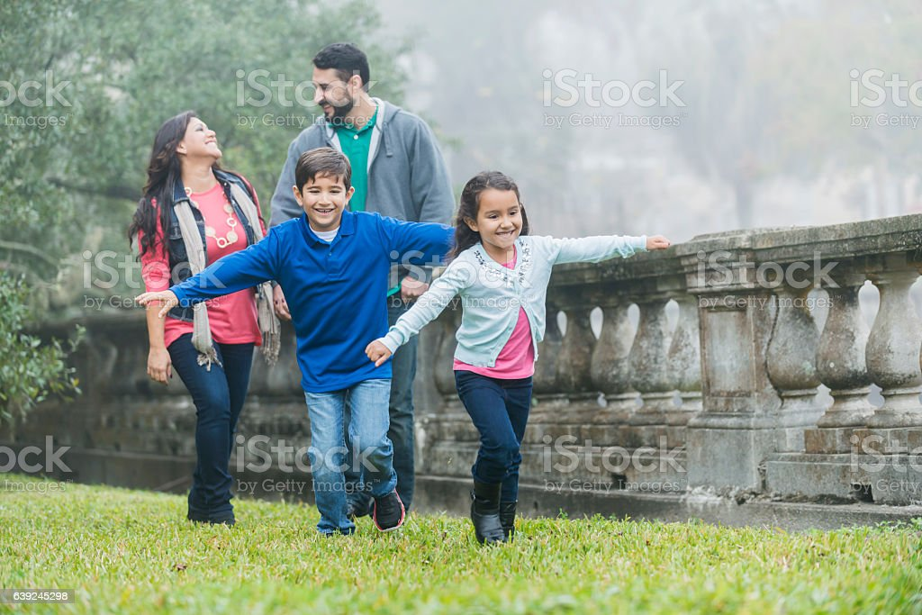 Family with two playful children taking a walk in park stock photo