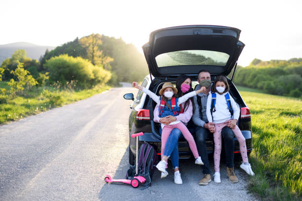 Family with two small daughters on trip outdoors in nature, wearing face masks. Front view of family with two small daughters on trip outdoors in nature, wearing face masks. road trip stock pictures, royalty-free photos & images