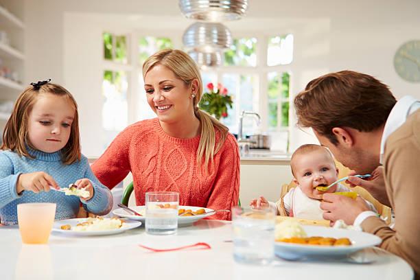 familie mit jungen baby essen mahlzeit wie zu hause fühlen. - kinderstuhl und tisch stock-fotos und bilder