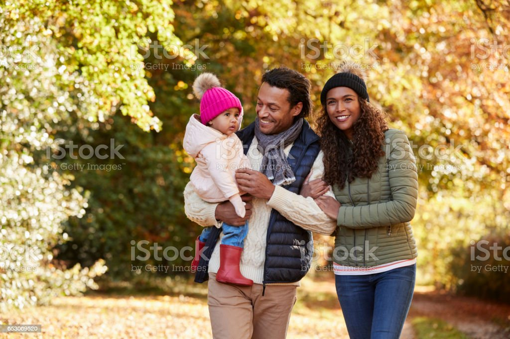Family With Young Daughter Enjoying Autumn Countryside Walk stock photo