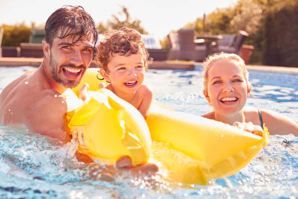 Family With Young Son Having Fun With Inflatable On Summer Vacation In Outdoor Swimming Pool stock photo