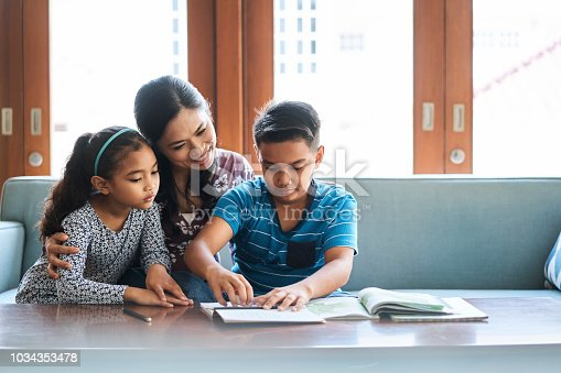 istock Family working on school project at home 1034353478