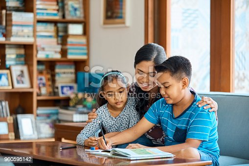 istock Family working on school project at home 960595142