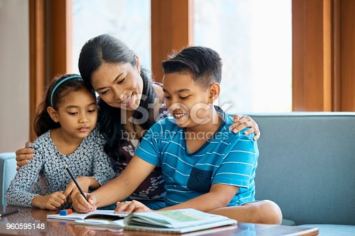 960595148 istock photo Family working on school project at home 960595148