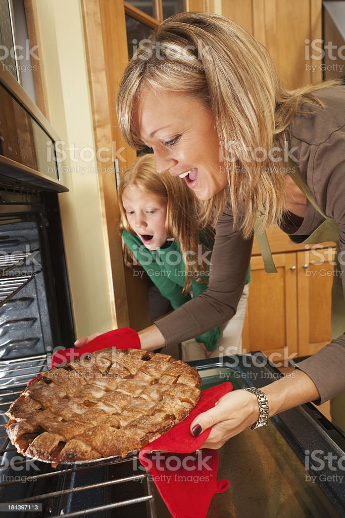 Family Working Together Baking Apple Pie in Home Kitchen Oven royalty-free stock photo