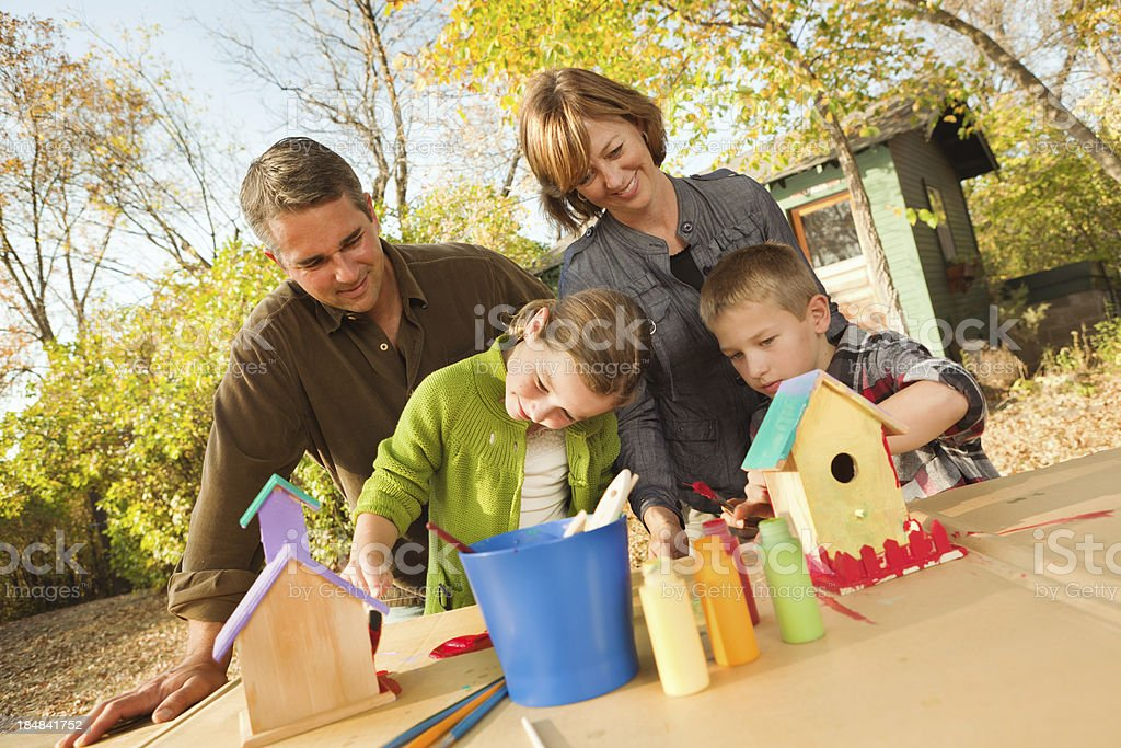 Family Working Together on a Birdhouse Painting Project Hz stock photo