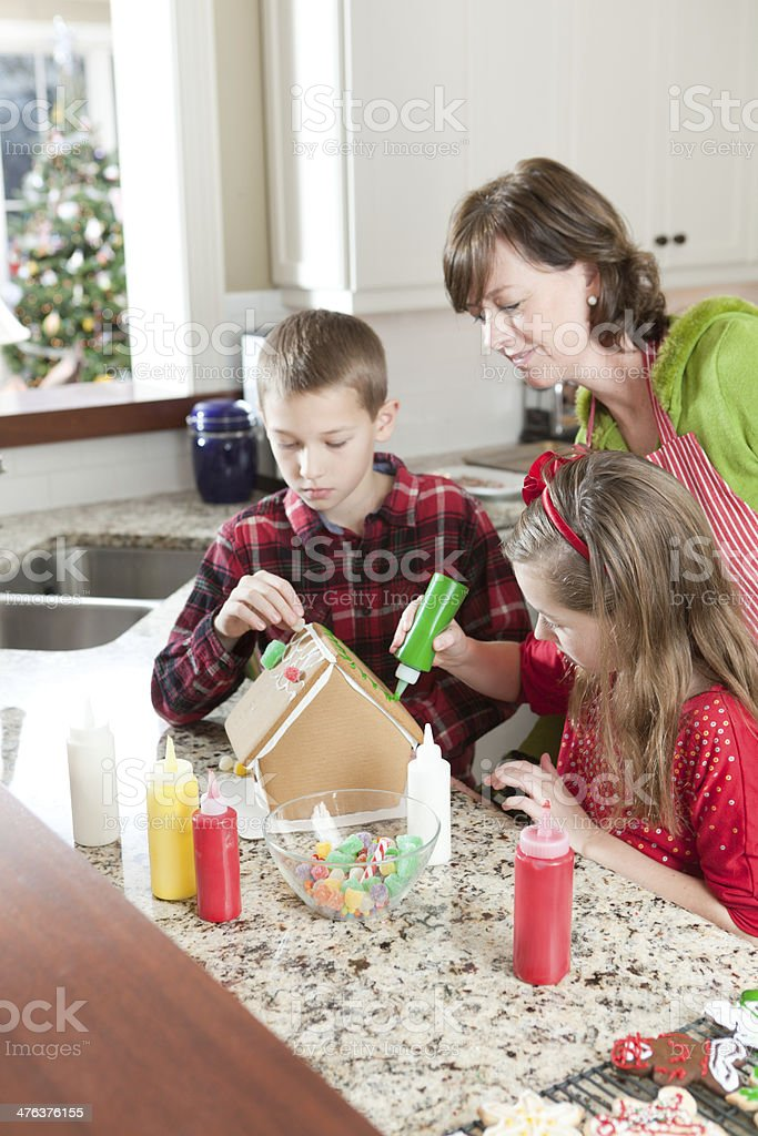 Family Working together on Christmas Gingerbread House Vt royalty-free stock photo