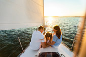 istock Family Yacht Sailing, Parents And Daughter Sitting On Deck, Back-View 1267273158
