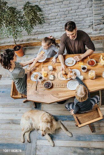 Above view of happy family having breakfast in the morning at dining table.