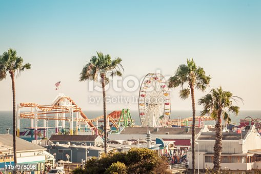 Famous amusement park with ferris wheeil in Santa Monica Los Angeles California in pastel ligt of sunset. Focus on palms