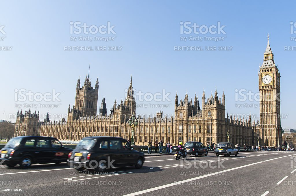 Famous black cab driving by Houses of Parliament royalty-free stock photo