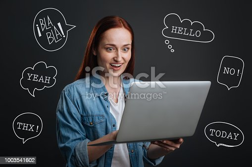 1003539592istockphoto Famous blogger holding a laptop and reading positive comments 1003541602