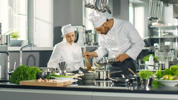 Famous Chef and His Female Apprentice Prepare Special Dish in a Modern Five Star Restaurant's Kitchen. Famous Chef and His Female Apprentice Prepare Special Dish in a Modern Five Star Restaurant's Kitchen. chef's whites stock pictures, royalty-free photos & images