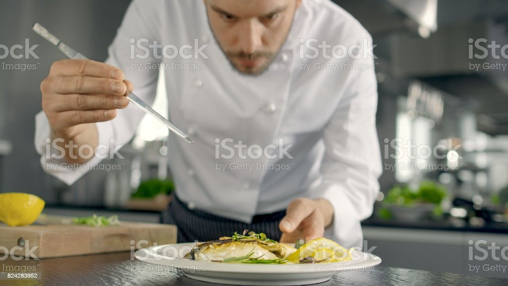 Famous Chef Decorates His Special Fish Dish with Some Greens. He Works in a Modern Kitchen. stock photo