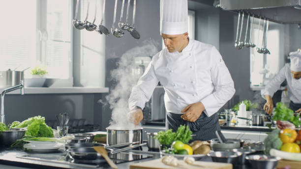 Famous Chef of a Big Restaurant Prepares Dishes with His Help of Cooks. Modern Kitchen is Made of Stainless Steel and Full of Cooking Ingredients. Famous Chef of a Big Restaurant Prepares Dishes with His Help of Cooks. Modern Kitchen is Made of Stainless Steel and Full of Cooking Ingredients. chef's whites stock pictures, royalty-free photos & images
