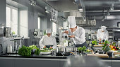 Famous Chef Works in a Big Restaurant Kitchen with His Help. Kitchen is Full of Food, Vegetables and Boiling Dishes. He is trying taste.