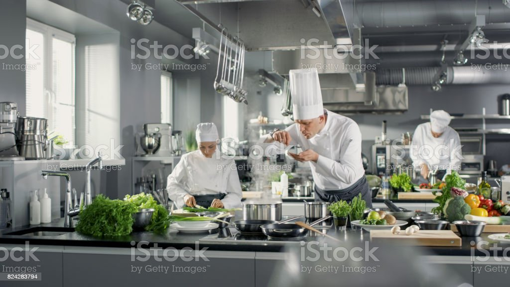 Famous Chef Works in a Big Restaurant Kitchen with His Help. Kitchen is Full of Food, Vegetables and Boiling Dishes. He is trying taste. stock photo