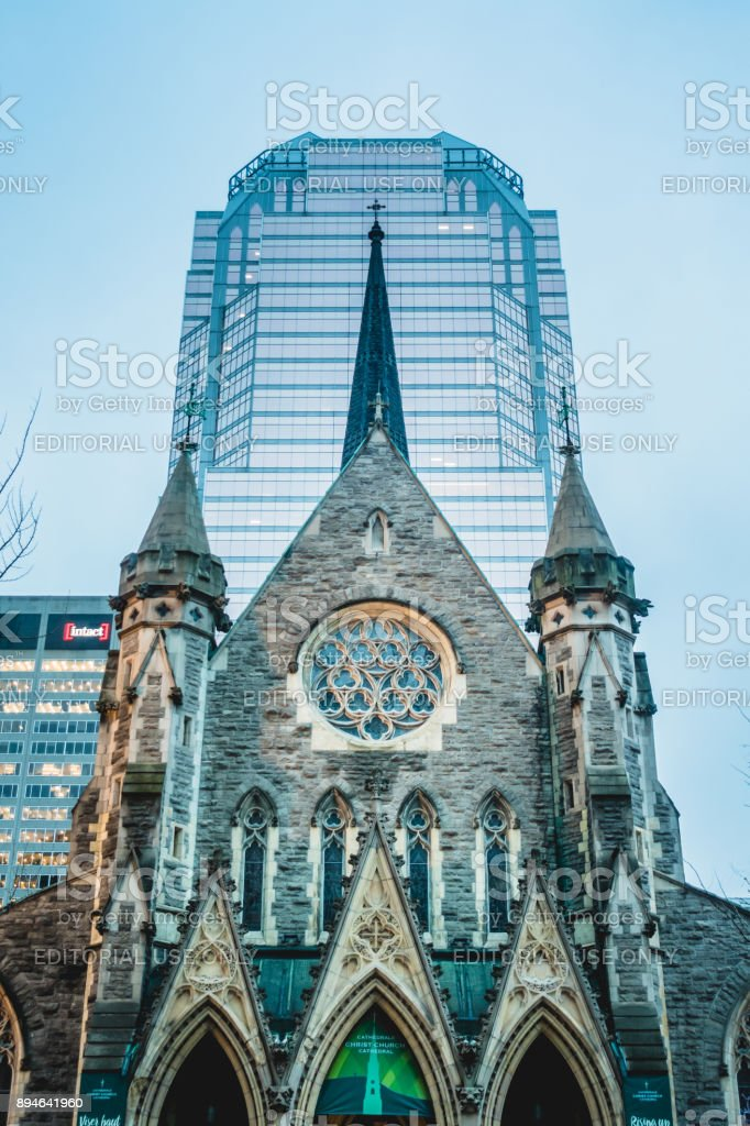 Famous Christ Church Cathedral on Ste-Catherine Street Downtown Montreal with Modern Symmetrical Architecture in Background stock photo
