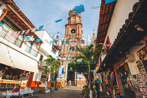 Puerto Vallarta, Mexico - December 28, 2016: Our Lady of Guadalupe Parish sits on a busy street filled with tourists and souvenir vendors.