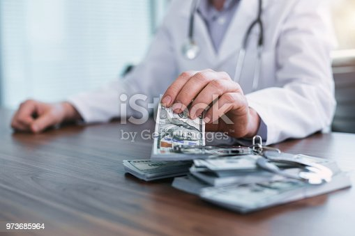 182362845 istock photo Famous doctor taking bribes in his office 973685964