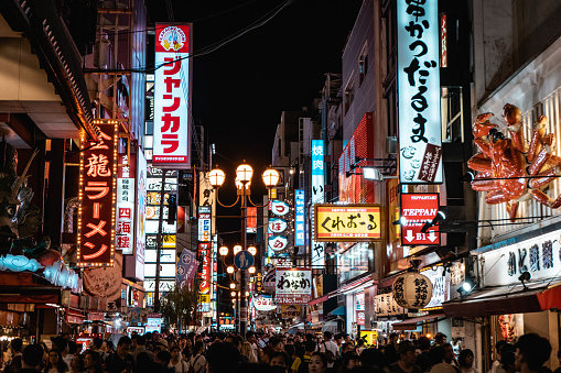 Famous Dotonbori shopping street of Osaka with thousands of people and neon signs