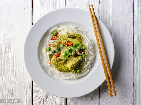 This Thai known in Thai as 'Gaeng Keow Wan Gai' dish is very famous and known all over the world and one of Thailand's popular signature dishes when it comes to Thai food. This dish consists of ingredients including a green herb-based base with fresh coconut milk, sweet basil, Thai aubergines, pea aubergines, chicken, and spicy fresh red chili. The combination of ingredients results in a sweet and spicy taste with a variety of complementary textures and is normally eaten together with fresh steamed Jasmine Thai rice or fresh rice noodles. The image was taken from directly above with the dish set on an old white worn textured wooden background with lots of grain and character.