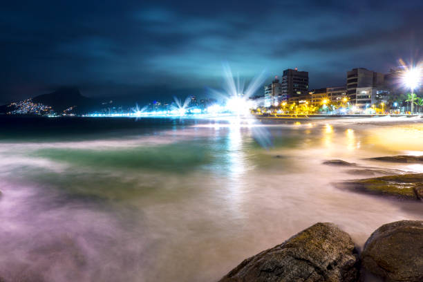 Famous Ipanema Beach At Night With Beautiful Lights And Slow Water Waves Over Rocks stock photo