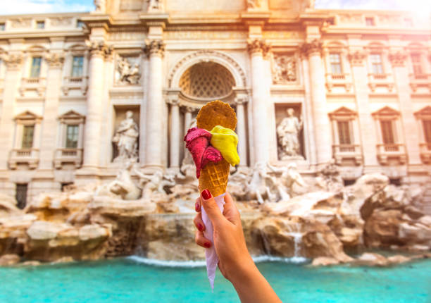 Famous Italian Gelato at Trevi Fountain Rome Hand holding colorful gelato in front of famous iconic Trevi Fountain at Rome, Italy. rome italy stock pictures, royalty-free photos & images