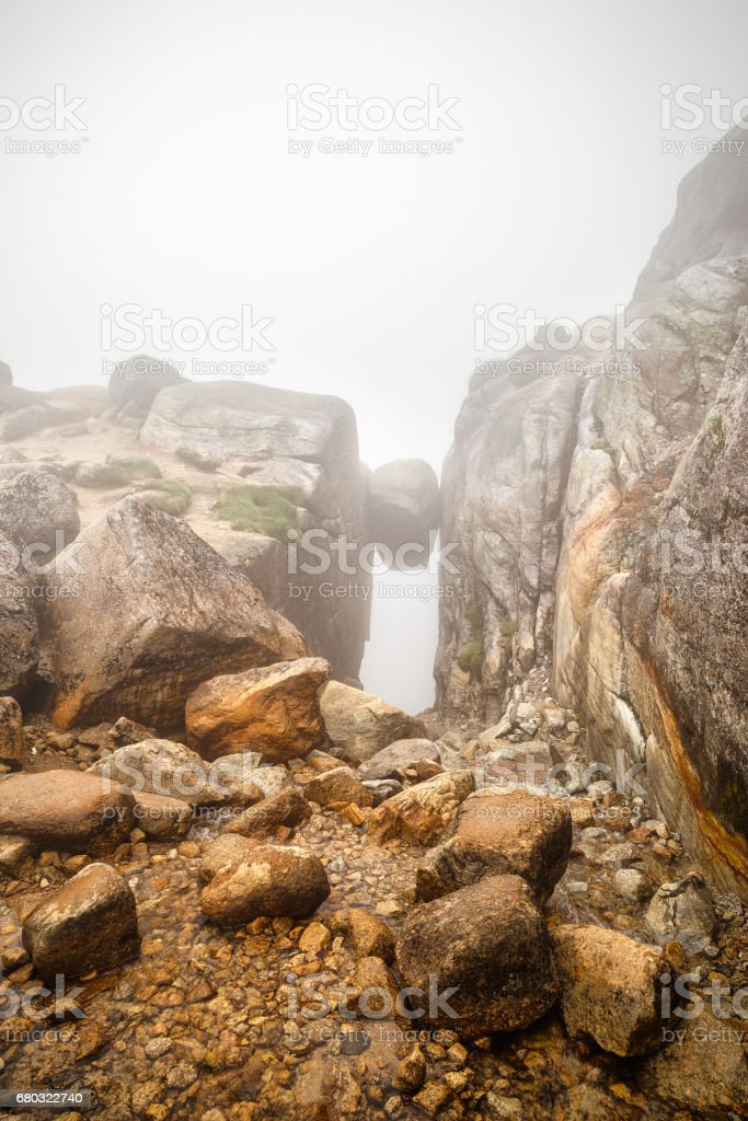 Famous Kjerag stone, hanging on the cliff between two high rocks on the Lysefjord coast. Norway. Popular travel destination in Norway, Europe. stock photo