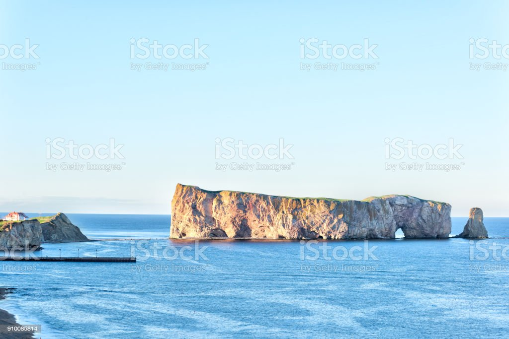 Famous large Rocher Perce rock in Gaspe Peninsula, Quebec, Gaspesie region, Canada at sunset, blue Saint Lawrence gulf water stock photo