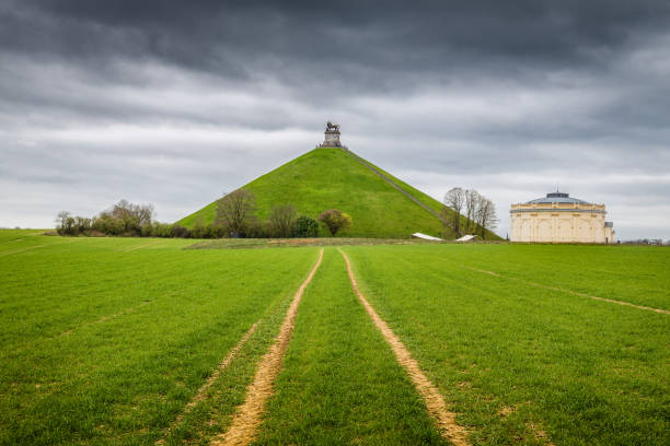 Famous Lion's Mound memorial site at the battlefield of Waterloo with dark clouds, Belgium Panorama view of famous Lion's Mound (Butte du Lion) memorial site, a conical artificial hill located in the municipality of Braine-l'Alleud comemmorating the battle of Waterloo, on a moody day with dark clouds in summer, Belgium. King William I of the Netherlands ordered its construction in 1820, and it was completed in 1826. battlefield stock pictures, royalty-free photos & images