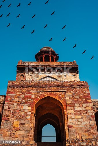 Close up of a huge gate structure at a fort made with red sandstone called Talaqi Darwaza with clear sky and a flock of birds in background.