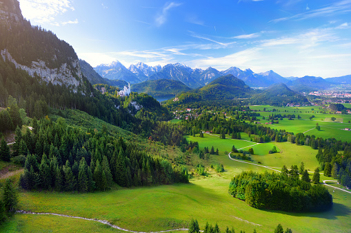 Famous Neuschwanstein Castle visible in the distance, located on a rugged hill above the village of Hohenschwangau in southwest Bavaria, Germany