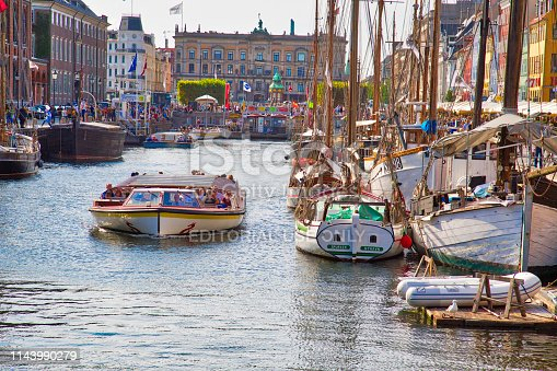 Copenhagen, Denmark-2 August, 2018: Famous Nyhavn (New Harbour) bay in Copenhagen, a historic 17 century European waterfront with colorful buildings. A starting point for boat and canal tours.