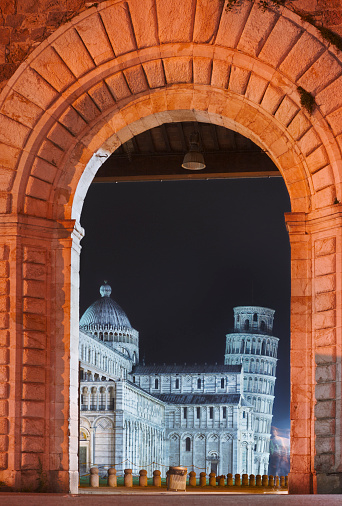 The famous Piazza dei Miracoli in Pisa is seen here from Piazza Manin. The tower (campanile) is thus unusually visible under an arch. Given the long-exposure time, one person moving is visible but not recognizable.