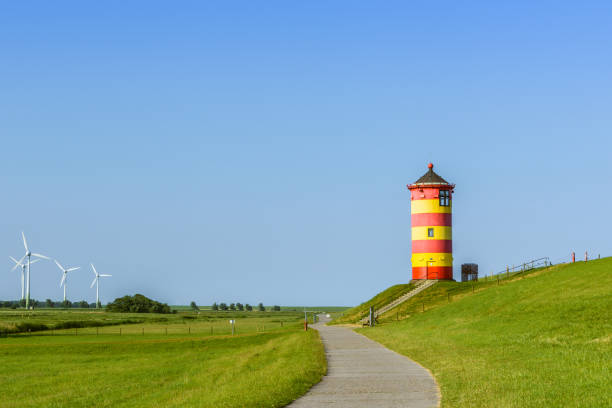 Famous Pilsum Lighthouse with Clear Blue Sky in East Frisia Near Greetsiel, Lower Saxony, Germany Walkway to the Pilsum Lighthouse on the dike on the East Frisian North Sea Coast in Lower Saxony, Germany, with wind turbines in the background. The lighthouse was built in 1891 and is located  near the village of Greetsiel. It became famous as one of the central locations of the movie Otto – Der Außerfriesische (
