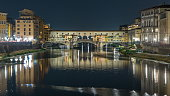 Famous Ponte Vecchio bridge timelapse over the Arno river in Florence, Italy, lit up at night. Reflection on water. Old houses on the side