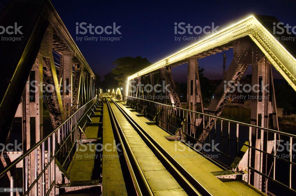 famous Railway bridge with yellow neon lamp at Kanchanaburi, Thailand with slective focus stock photo