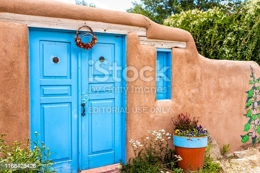 Ranchos de Taos, USA - June 19, 2019: Famous St Francic Plaza in New Mexico with turquoise adobe architecture color decorations on door