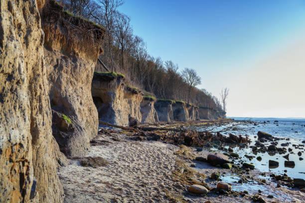 słynny stromy klif wybrzeża z wyprane jaskinie na niemieckiej wyspie poel w morzu bałtyckim w pobliżu wismar, błękitne niebo z kopią przestrzeni - erodowany zdjęcia i obrazy z banku zdjęć